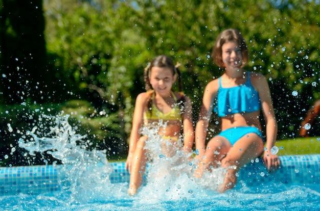 Aptidão do verão, crianças na piscina se divertem e espirram na água, crianças em férias em família