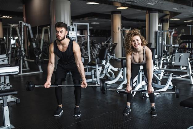 Aptidão e jovem casal se exercitando na academia com pesos de barra