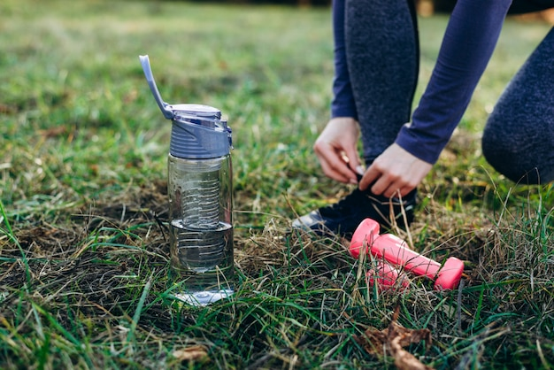 Aptidão no parque, garota amarrando o sapato, garrafa de pé e halteres, close-up.