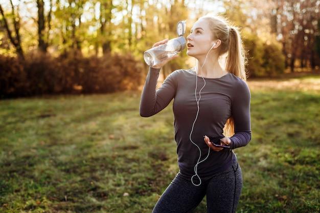 Aptidão no parque, garota bebendo água, segurando o smartphone e fones de ouvido na mão.