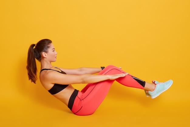Aptidão praticando da mulher desportiva nova interior, fazendo o exercício do barco, malhando, vestindo sutiã preto e leggins vermelhos, comprimento total, isolado no amarelo, vista lateral.