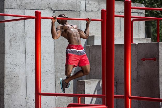 Apto atleta fazendo exercícios no estádio. homem afro-americano ao ar livre na cidade