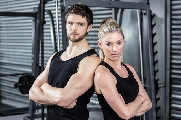 Apto casal com braço cruzado no ginásio crossfit