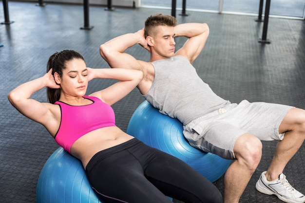 Apto casal fazendo abdominais na bola de fitness no ginásio