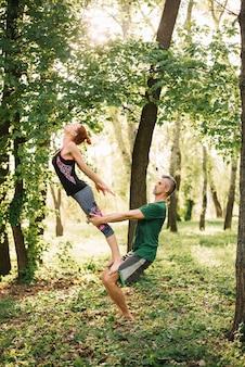 Apto casal fazendo equilíbrio de acroyoga no parque