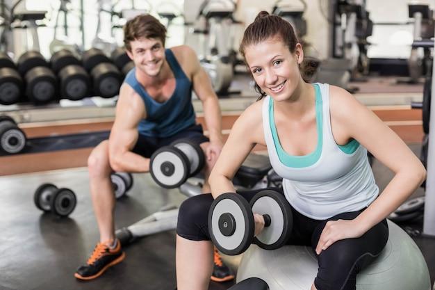 Apto casal levantando halteres no ginásio
