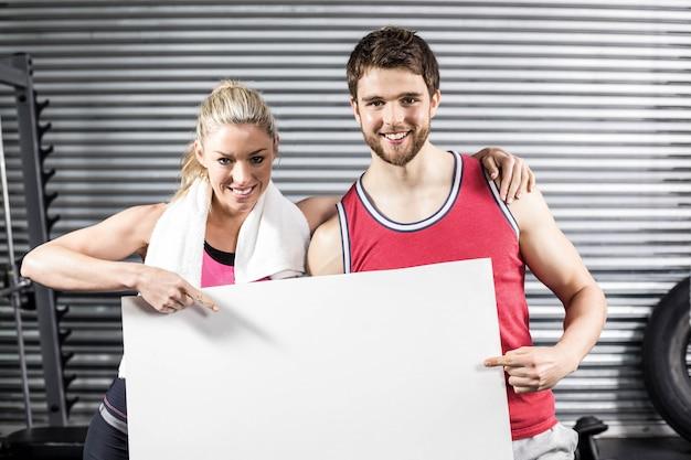 Apto casal segurando papel em branco no ginásio crossfit