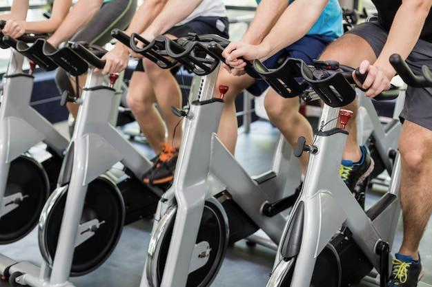 Apto grupo de pessoas usando bicicleta ergométrica juntos no ginásio