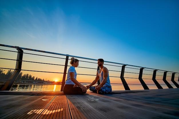 Apto jovem casal fazendo ioga pose de lótus estilo de vida saudável pessoas atividade de esporte ao ar livre em família vac ...