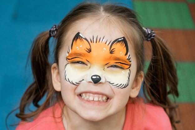 Aquagrim no rosto da criança. retrato de uma menina com um padrão de chanterelle no rosto. entretenimento para as férias. tatuagem para uma criança. criatividade infantil.
