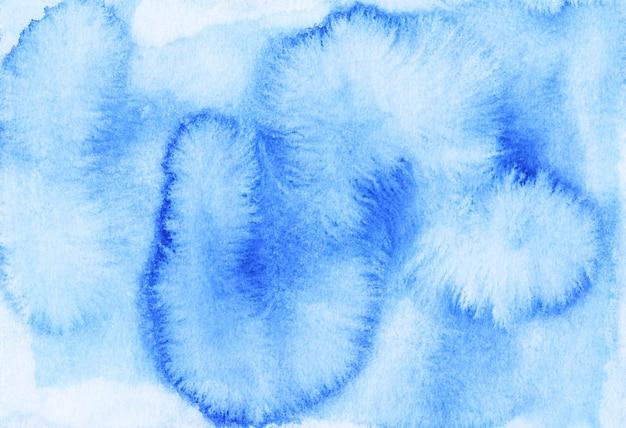 Aquarela manchas azuis claras sobre fundo de papel. cenário de pintados à mão.