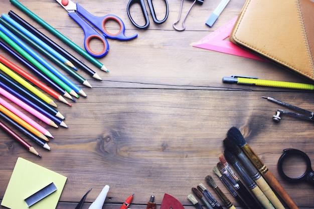 Aquarela, pincéis, lápis e tesouras na mesa