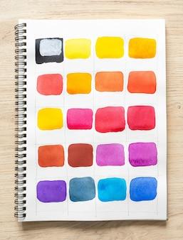 Aquarela tinta especial em papel de caderno branco com fundo de madeira. coleção de tonalidades coloridas em papel branco. conjunto de pincel aquarela multicolorido. fechar-se.