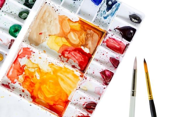 Aquarela tintas com pincel isolado no fundo branco. conceito de arte e hobby.