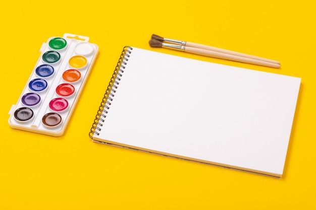 Aquarela tintas e pincéis com álbum para desenho isolado em fundo amarelo
