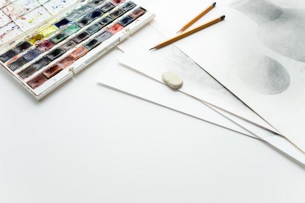 Aquarela tintas, lápis, borracha, desenhos em uma mesa branca. coloque para copiar o espaço.