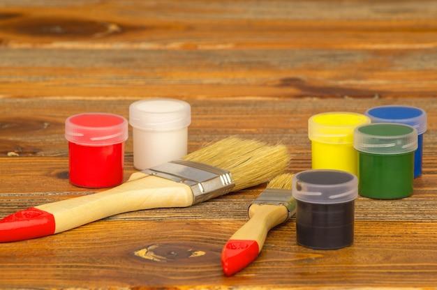 Aquarelas de várias cores em potes de plástico e pincéis sobre uma mesa de madeira.