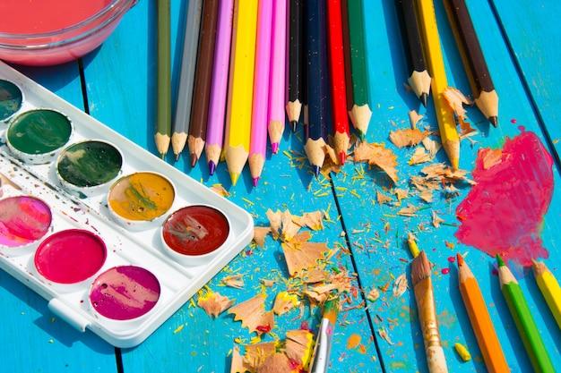 Aquarelas e lápis sobre fundo azul de madeira