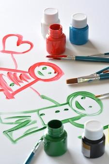 Aquarelas e pincéis com desenhos de crianças em tela branca