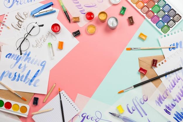 Aquarelas, pincéis, óculos, caneta pincel, tintas, folhas de prática de letras e outros artigos de papelaria e arte