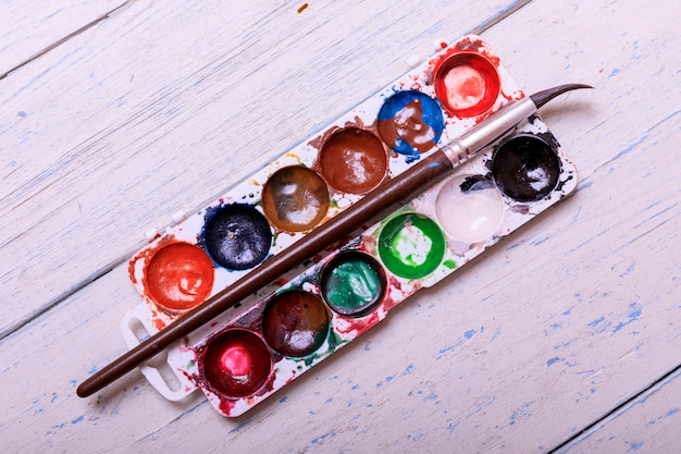 Aquarell aquarela profissional pinta em caixa com pincéis na prancha de madeira branca velha