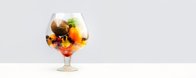 Aquário com alimentos saudáveis, frutas, vegetais e frutas vermelhas (morango, morango, framboesa, coco, brócolis, pimenta, laranja, limão) suco suculento em uma parede branca