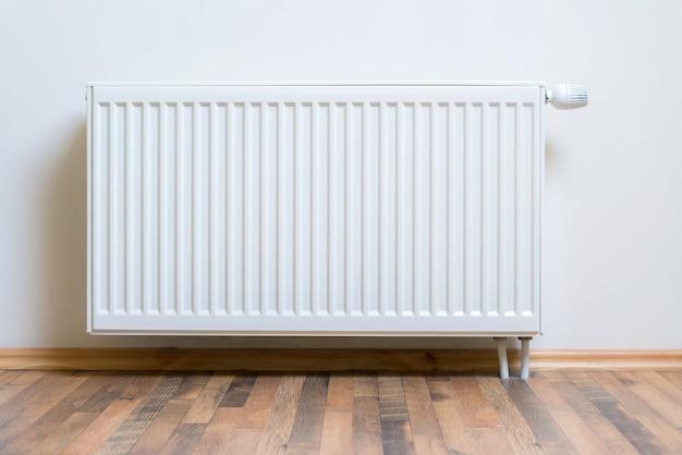 Aquecedor de radiador em casa na parede branca em piso de madeira de lei. equipamento de aquecimento ajustável para apartamento e casa