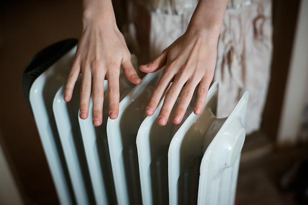 Aquecendo as mãos sobre um radiador.