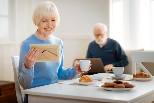 Aquecendo. avó tomando café, comendo croissant e planejando o dia antes de chegar dos netos