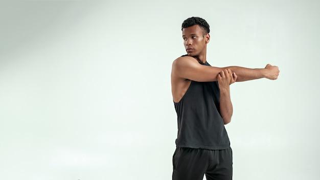 Aquecendo o jovem homem afro-americano forte, esticando o braço em pé contra um fundo cinza