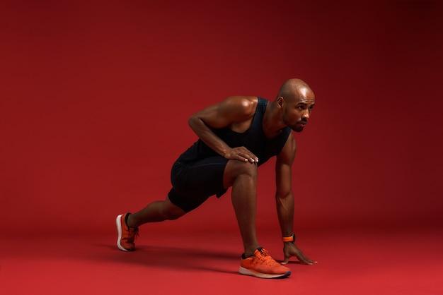 Aquecimento antes de treinar jovem e forte africano em roupas esportivas, alongamento em pé