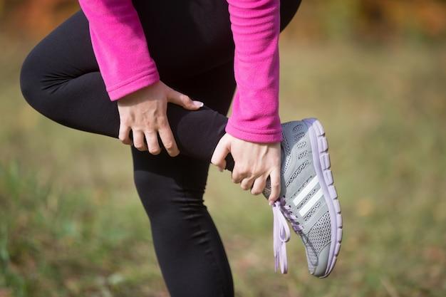 Aquecimento ao ar livre no outono, segurando um tornozelo