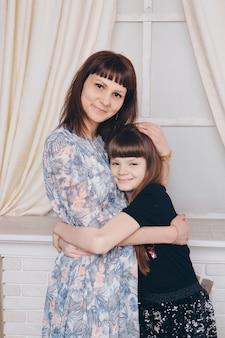 Aquecimento e relaxamento perto da lareira. mãe e filha abraçando. conceito de família, maternidade, interior, casa, infância, dia das mães, dia das crianças