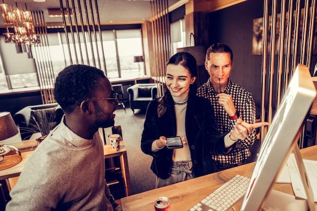 Aqui está. menina morena gentil com um sorriso no rosto enquanto aponta para o computador durante uma conversa