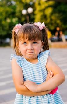Aqui está uma menina em um parque público. a criança fica ofendida e chateada. mimos e desobediência. paternidade.