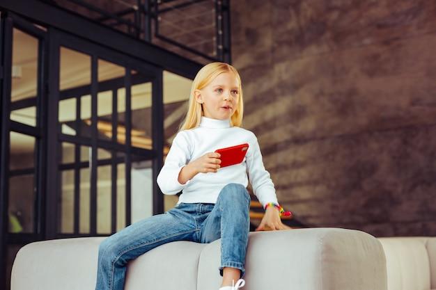 Aqui estou. criança alegre olhando para a frente e segurando o smartphone na mão direita