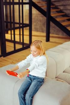 Aqui estou. menina encantada expressando positividade ao usar o smartphone