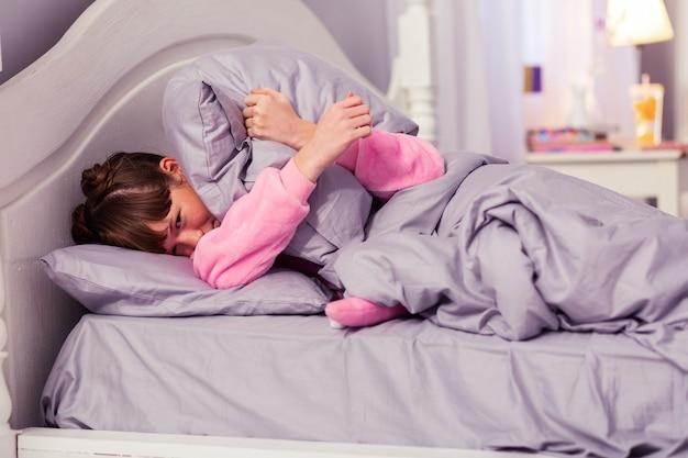 Aqui estou. menina encantadora deitada em sua cama enquanto descansa pela manhã