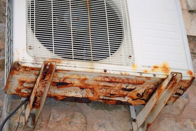 Ar condicionado antigo com corrosão, na parede, ao ar livre