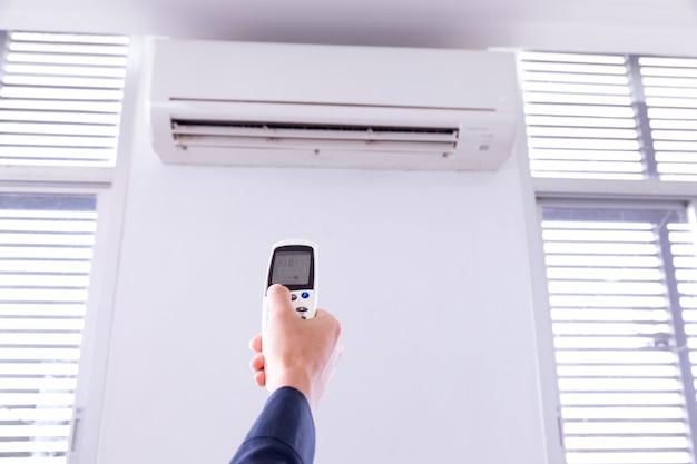 Ar condicionado com controle remoto, dentro da sala com o homem operando o controle remoto.