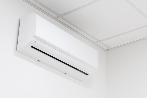 Ar condicionado de aquecimento e resfriamento branco na parede branca no escritório ou em casa.