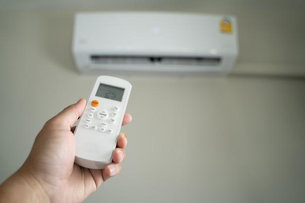 Ar condicionado na parte superior da sala, operando o controle remoto aberto, economia de energia do ar condicionado