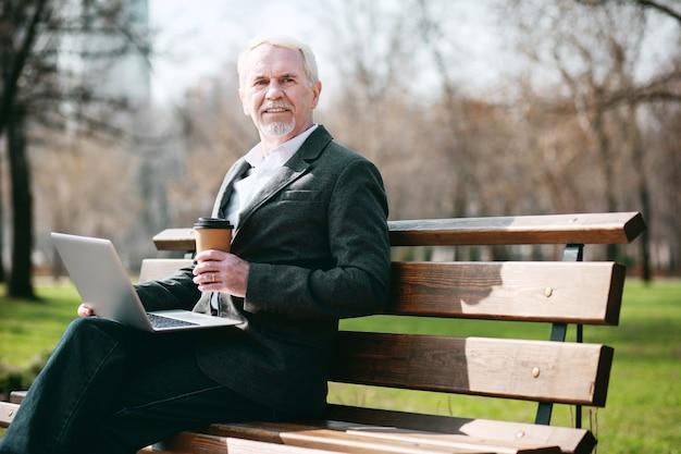 Ar fresco. ângulo baixo do empresário maduro e alegre usando o laptop enquanto está sentado no banco