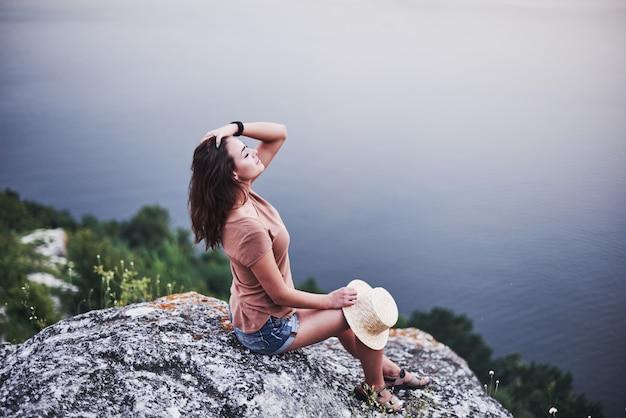 Ar fresco. garota turística posando na borda de uma montanha com um lago de águas claras ao fundo