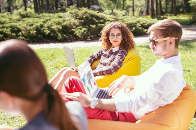 Ar livre. menina de cabelos cacheados encantada trabalhando em seu laptop e seu colega sentado nela