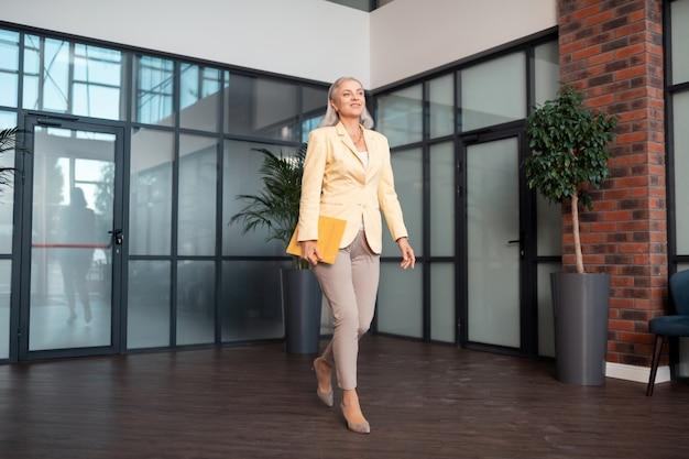 Ar profissional. mulher idosa atraente e satisfeita com uma jaqueta amarelo-claro e uma pasta de papel caminhando pelo escritório
