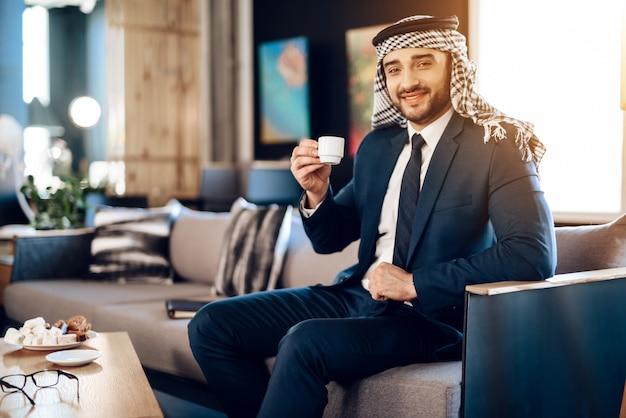 Árabe é beber café no sofá no quarto de hotel.