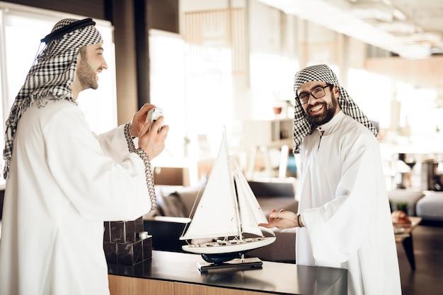 Árabe fazendo foto com modelo de navio para amigos