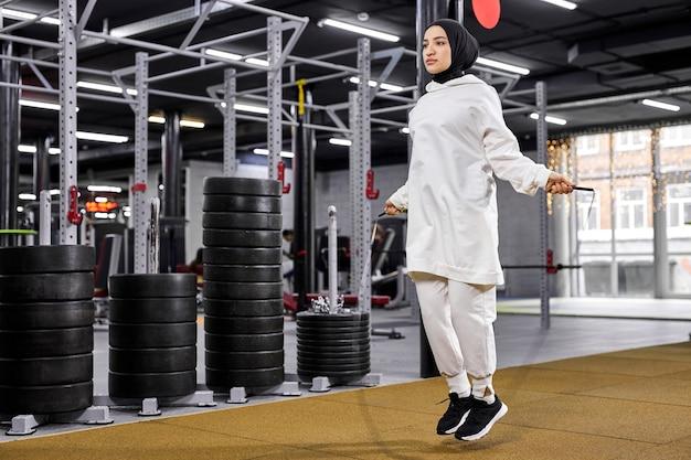 Árabe fêmea em hijab pulando com pular corda, magro e forte fêmea envolvida em esportes, academia moderna, conceito de fitness