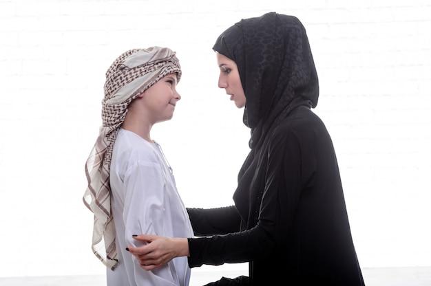 Árabe mãe e filho posando dentro de casa.